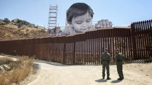 JR erected monumental photograph of a child just behind the California border fence, looking into Tecate, Mexico