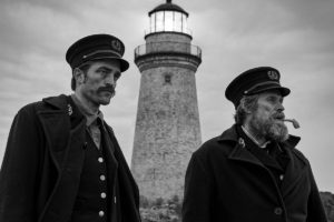 Willem Dafoe and Robert Pattinson in Robert Eggers' The Lighthouse, reviewed at Riot Material magazine.