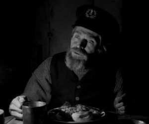 Willem Dafoe in Robert Eggers' The Lighthouse, reviewed at Riot Material magazine.